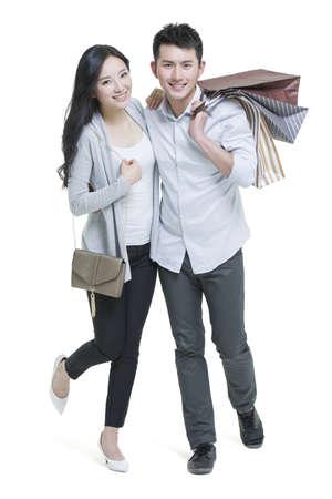 Pares novos felizes com sacos de compras