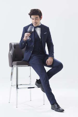 Elegant young man enjoying red wine