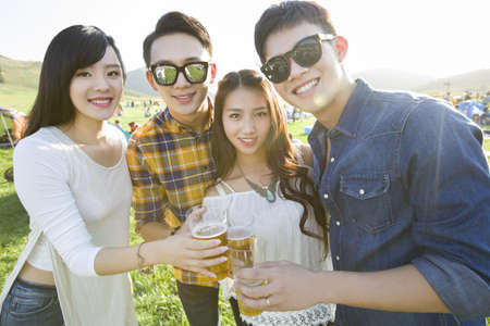 looking away from camera: Happy Chinese friends drinking beer together