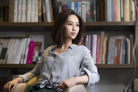 Young businesswoman sitting in study LANG_EVOIMAGES