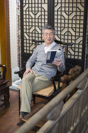 legs crossed at knee: Senior man reading book