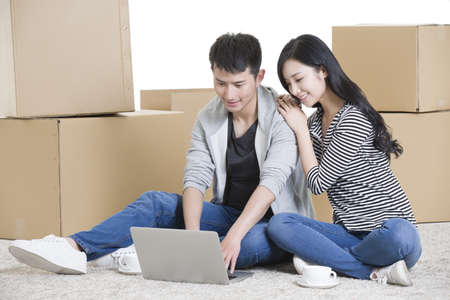 cardboard only: Young couple using laptop on floor