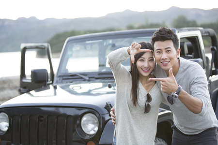 looking away from camera: Young Chinese couple and jeep