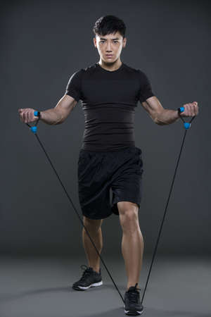 self conscious: Young man exercising with resistance band