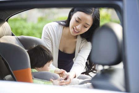transportation: Mother fastening seat belt for daughter