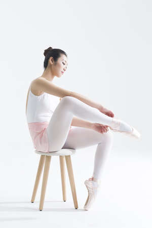 expertise concept: Ballet dancer tying up pointe shoes LANG_EVOIMAGES