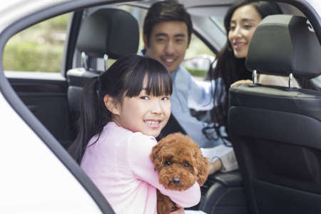 transportation: Happy young family with their pet dog sitting in car LANG_EVOIMAGES