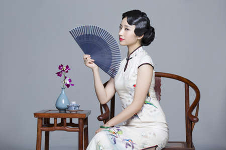 Young beautiful woman in traditional cheongsam with folding fan LANG_EVOIMAGES