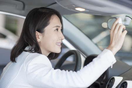 transportation: Young woman choosing car in showroom