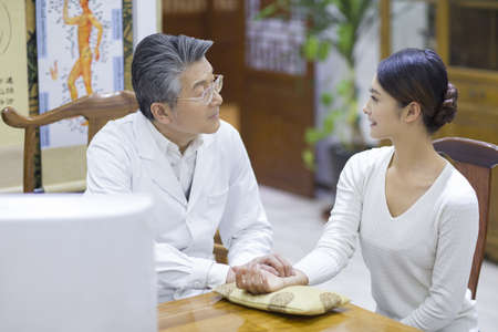Senior Chinese doctor taking the pulse of patient