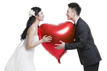 falling out: Happy bride and groom holding a heart-shaped balloon
