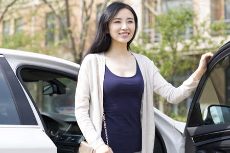 transportation: Young woman getting out of a car LANG_EVOIMAGES