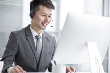 Chinese businessman working in office with headset LANG_EVOIMAGES
