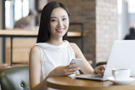 technology: Young Chinese woman working with laptop in café