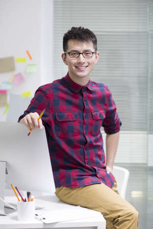 Portrait of young Chinese man in office