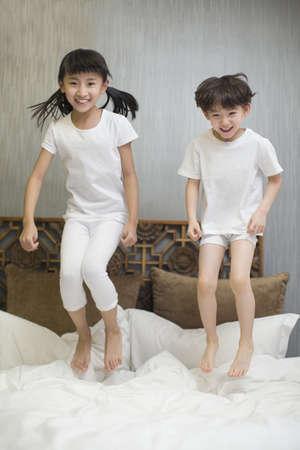 Little children jumping on bed