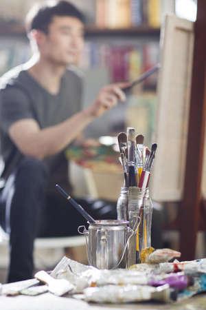 easel: Artist painting in his studio