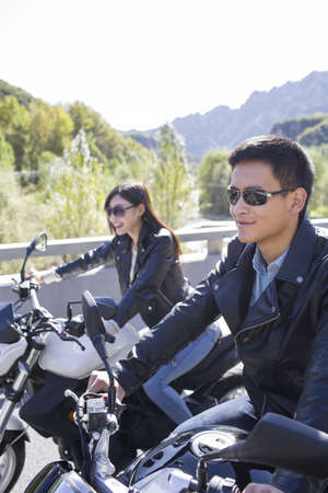 close range: Young Chinese couple riding motorcycle together
