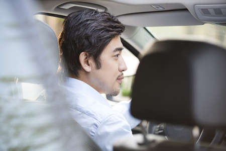 drivers seat: Young man driving car LANG_EVOIMAGES