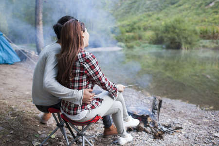 close range: Young Chinese couple sitting beside campfire preparing food