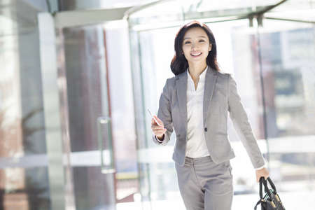 Businesswoman holding a smart phone walking