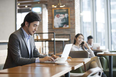 Chinese businessman working with laptop in café LANG_EVOIMAGES
