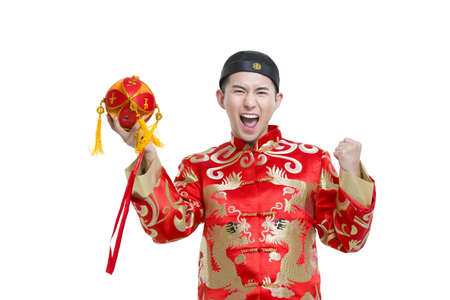 Young groom in Tang suit holding a embroider ball LANG_EVOIMAGES