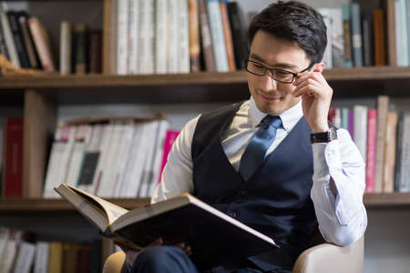 Young businessman reading book in his study LANG_EVOIMAGES