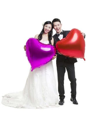 Happy bride and groom holding heart-shaped balloons
