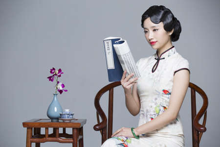 Young beautiful woman in traditional cheongsam reading book