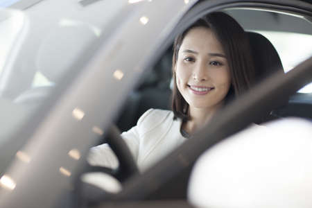 drivers seat: Young woman choosing car in showroom