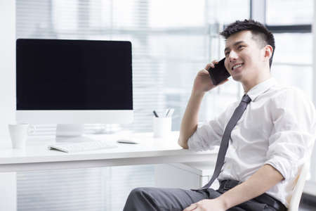 Chinese businessman talking on the phone in office LANG_EVOIMAGES