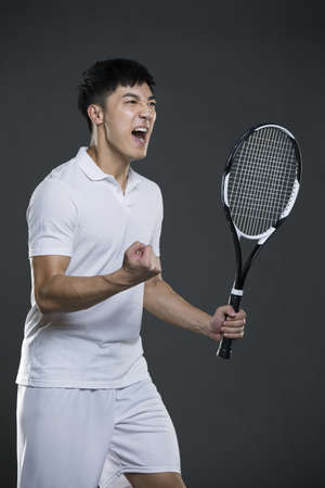 self conscious: Young man cheering with tennis racket