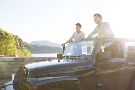 close range: Chinese friends having fun in a jeep LANG_EVOIMAGES