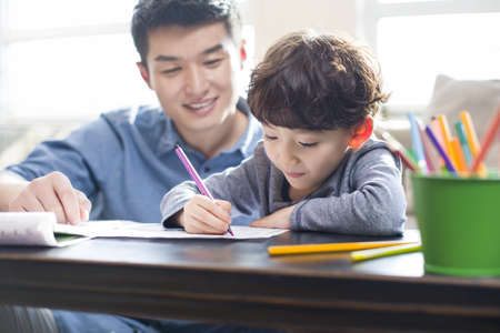 waist down: Young father helping son with homework