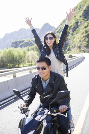 swerving: Young Chinese couple riding motorcycle together