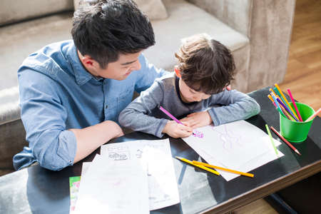 sit down: Young father helping son with homework