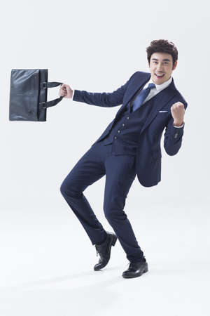 Happy young businessman with briefcase