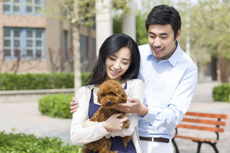 Happy young couple with their pet dog