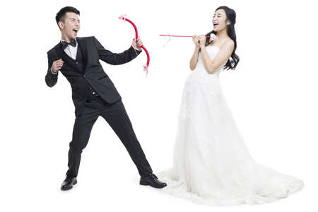 Happy bride and groom with bow and arrow LANG_EVOIMAGES