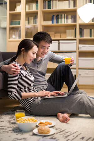 home life: Young couple using laptop in living room