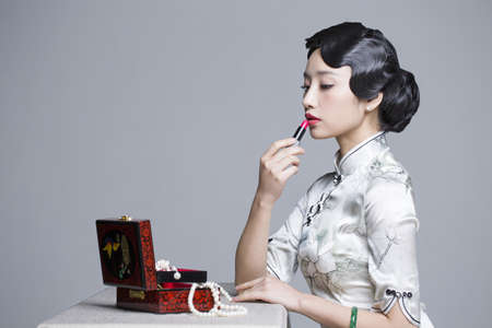 indian style sitting: Young beautiful woman in traditional cheongsam applying lipstick