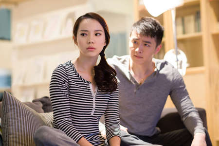 Young couple arguing on living room sofa