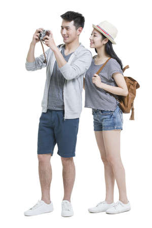 looking away from camera: Happy young couple traveling with camera