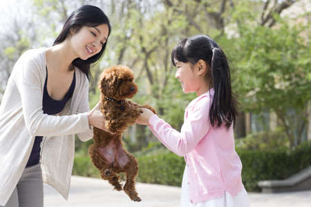 Happy young mother and daughter with their pet dog