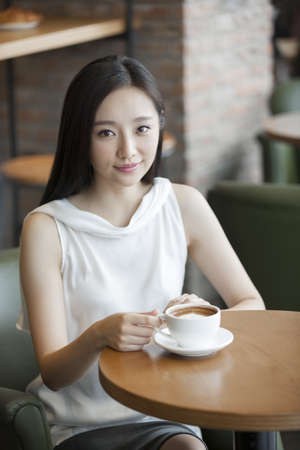Young Chinese woman drinking coffee in café LANG_EVOIMAGES