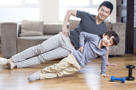 Young father and son exercising at home LANG_EVOIMAGES