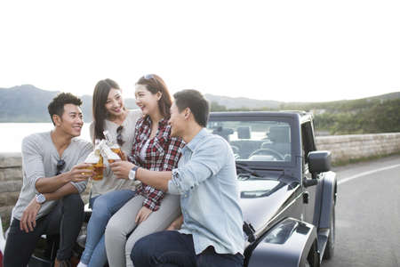close range: Happy Chinese friends drinking beer on a jeep