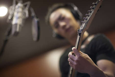 plucking: Young man singing with guitar in recording studio LANG_EVOIMAGES