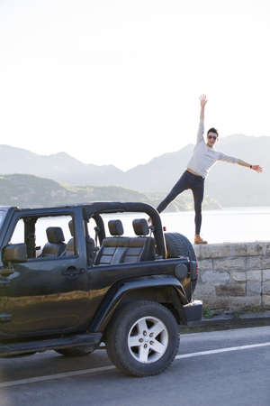 looking away from camera: Young Chinese man and jeep